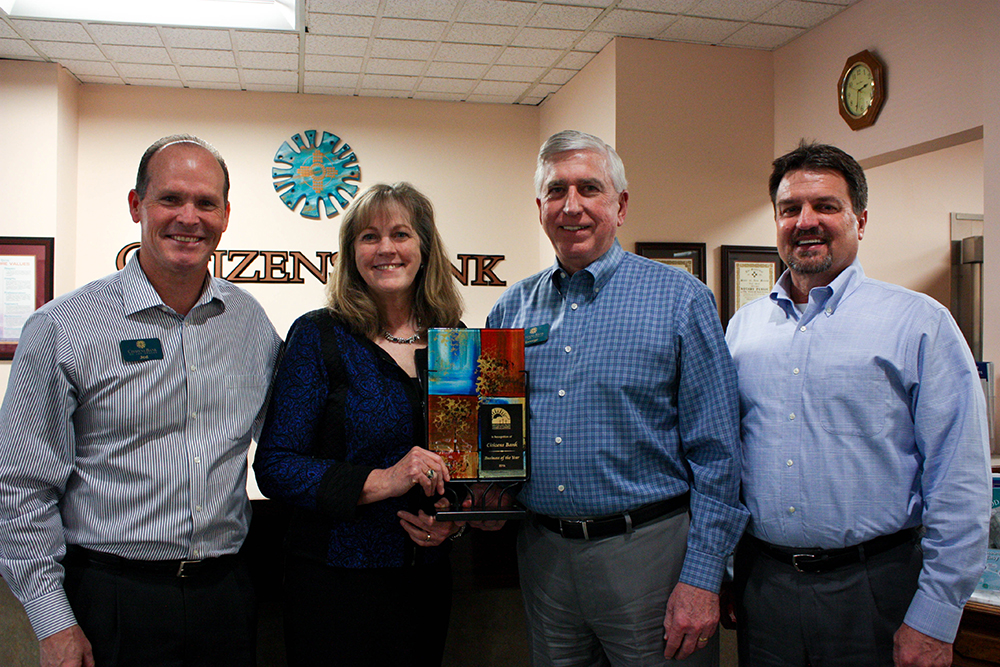 Picture of executive management holding the award.
