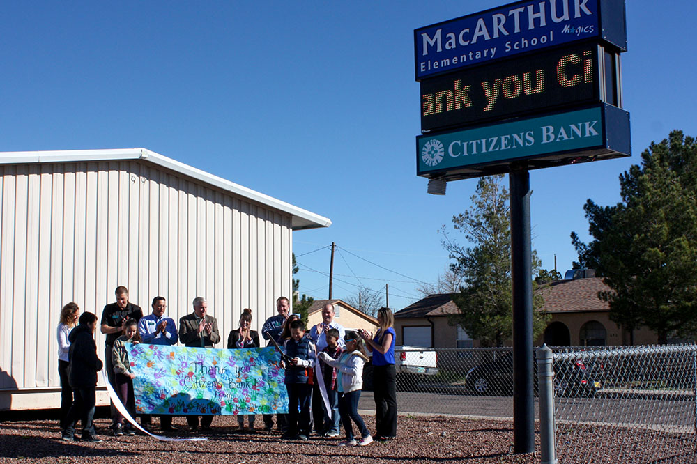 Picture of staff and students clapping after the ribbon is cut. Donated sign in the foreground.