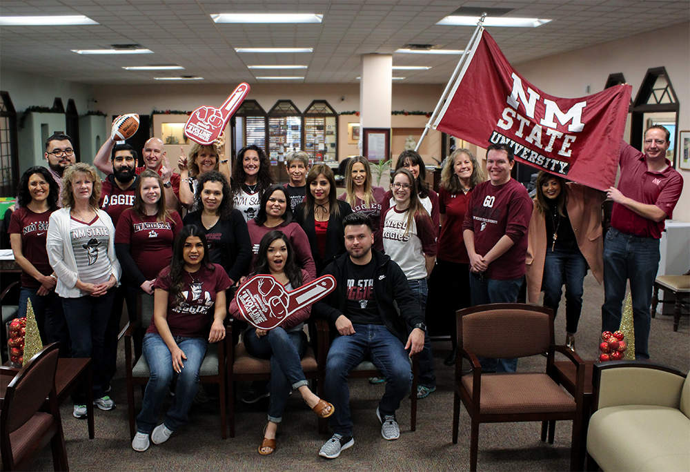 Picture of staff members wearing NMSU Aggie gear.