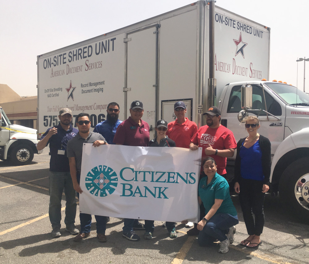 bank staff and ADS staff holding a bank banner in front of a shred truck